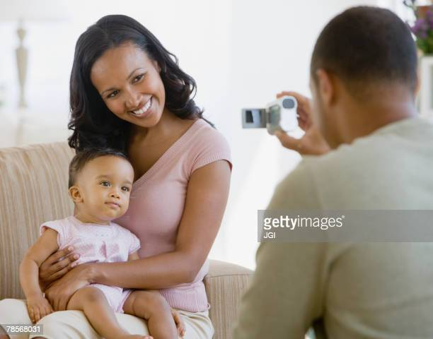 African American father taking photograph of family