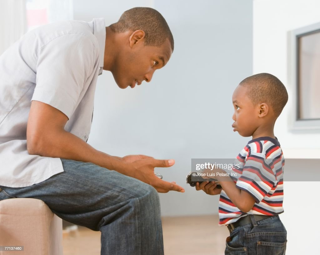 African American father talking to son : Stock Photo