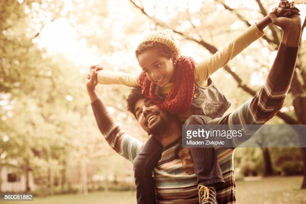 African American father with daughter. Little girl sitting on father shoulders.