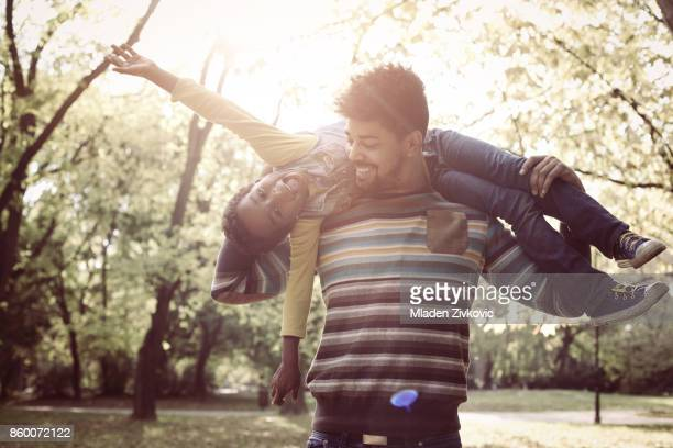 African American father with daughter on meadow. Girl lying on father shoulders.