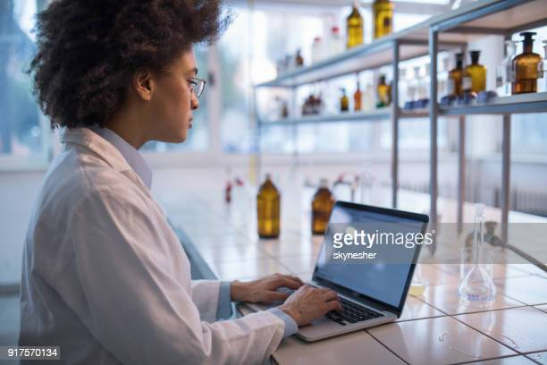 African American female biotechnologist working on laptop in a laboratory.
