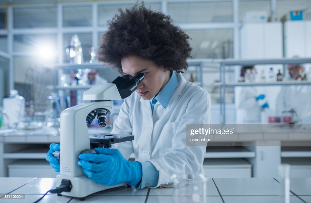 African American female doctor looking through a microscope while working on scientific research in laboratory. : Stock Photo