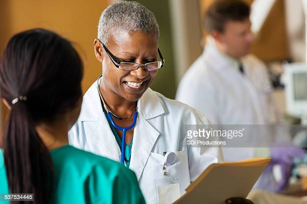 African American female doctor reading patient chart with hospital nurse