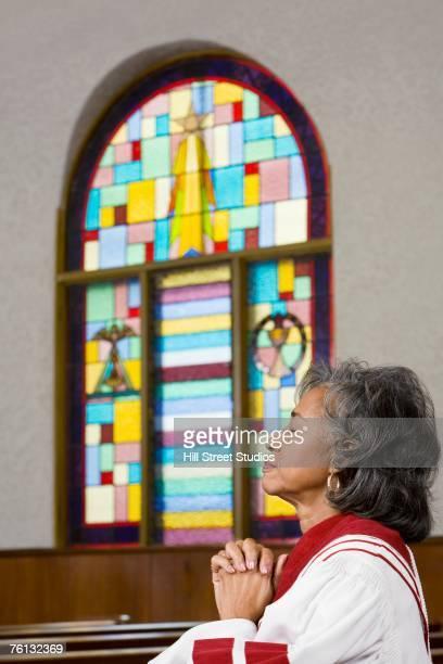 african american female reverend praying - mulher orando de joelhos imagens e fotografias de stock