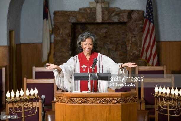 African American female Reverend preaching in church