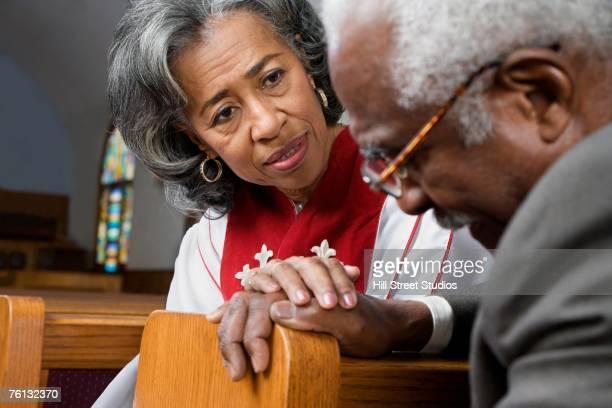 African American female Reverend talking to parishioner