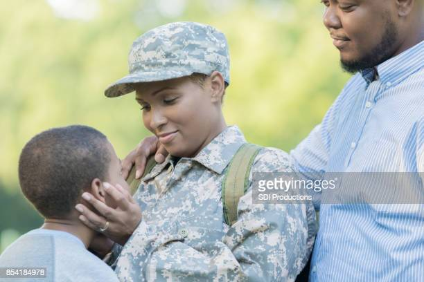 african american female soldier hugs family before deployment - military spouse stock pictures, royalty-free photos & images