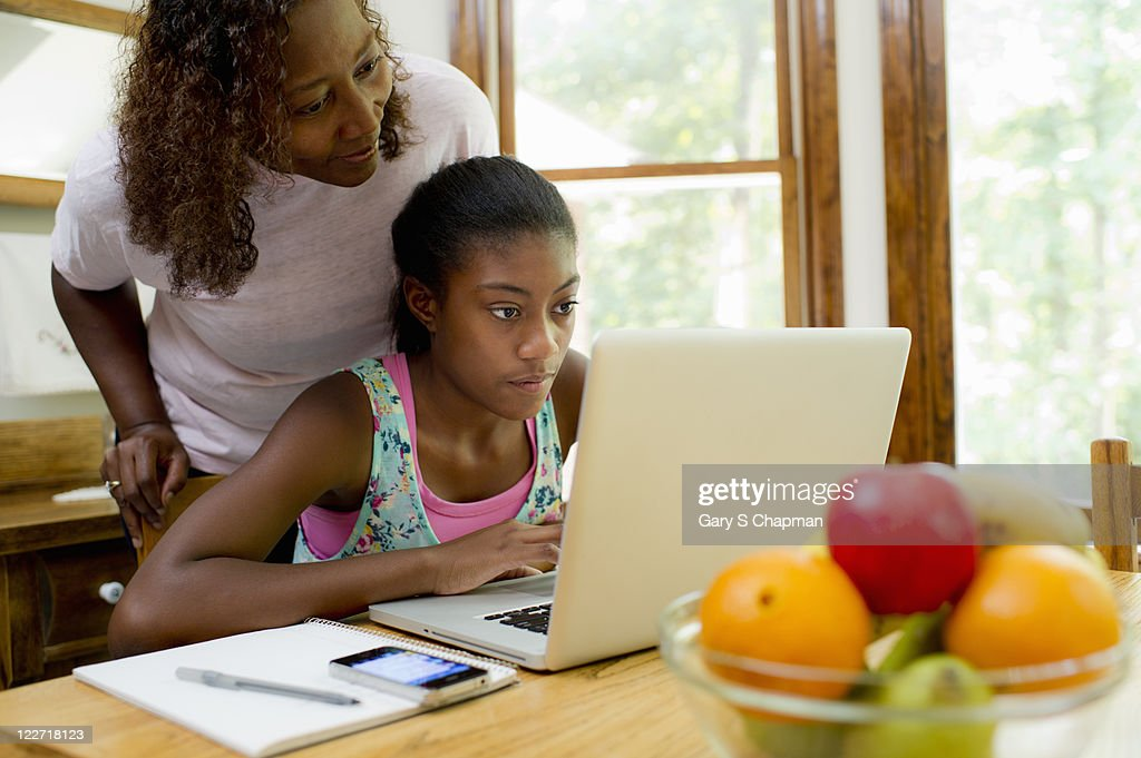African American female teen studying with mom : Stock Photo