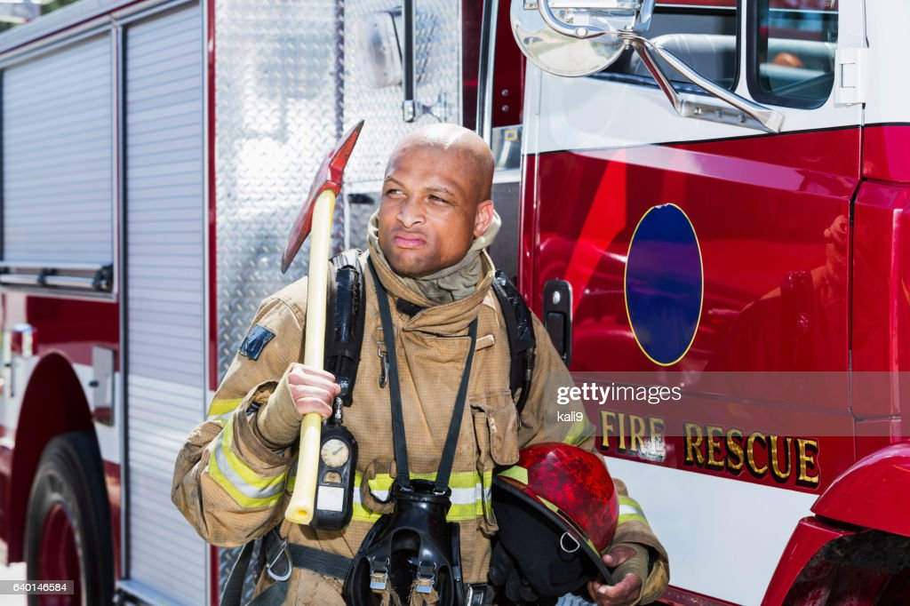 African American fire fighter carrying axe : Stock Photo