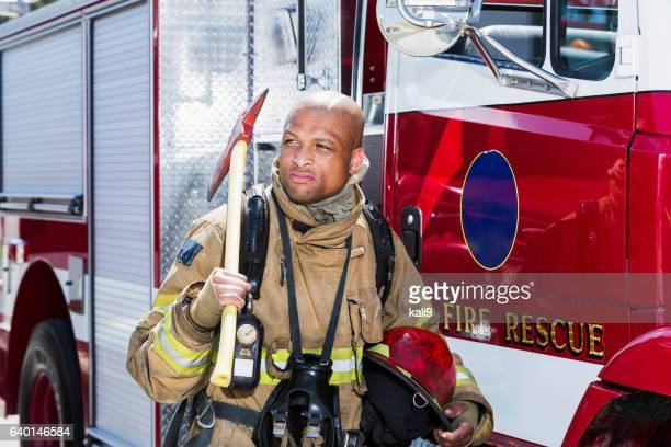African American fire fighter carrying axe