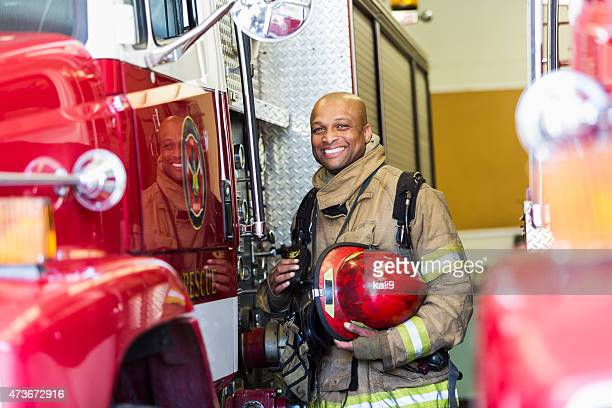 african american fire fighter standing next to truck - one mid adult man only stock pictures, royalty-free photos & images