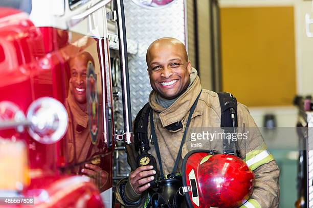 African American fire fighter standing next to truck