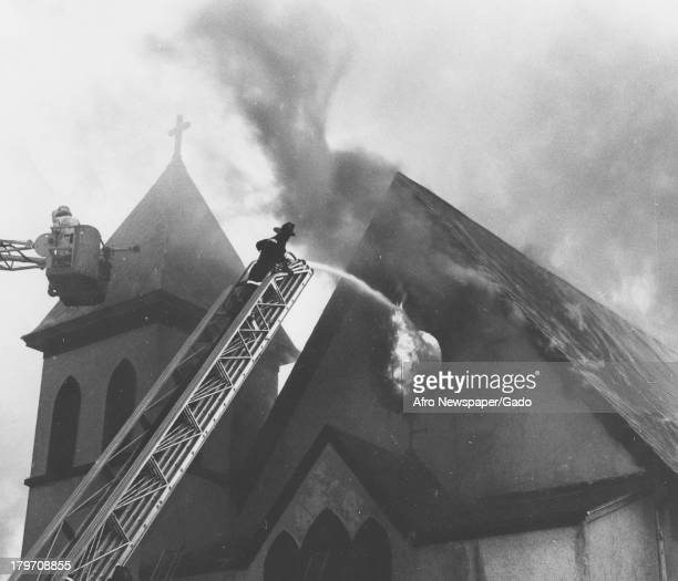 African American fire fighters work to put out a fire at Mt Zion Methodist church Baltimore Maryland 1965