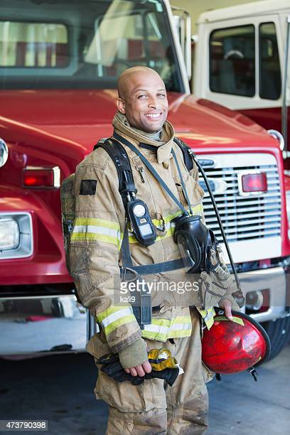 african american fireman at fire station - fire station stock photos and pictures