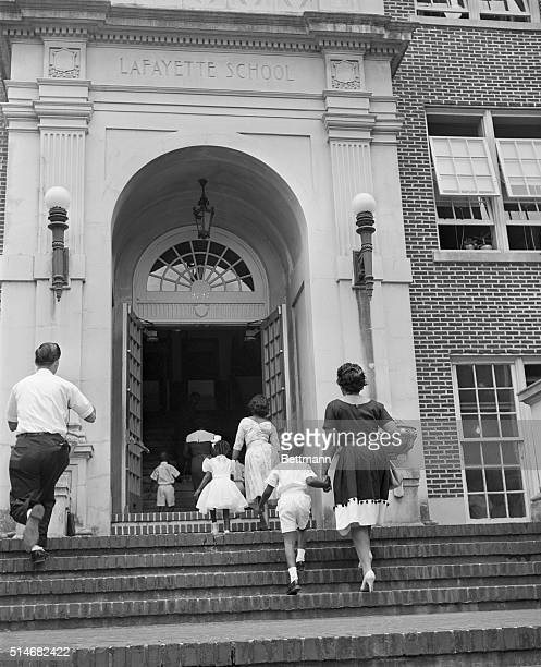 African American first graders and their mothers enter Lafayette School in New Orleans, Louisiana to register for classes at the newly desegregated...