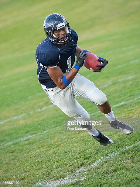 african american football player carrying ball - safety american football player stock pictures, royalty-free photos & images