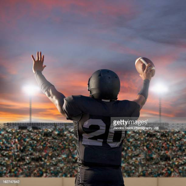 african american football player holding ball - safety american football player stock pictures, royalty-free photos & images