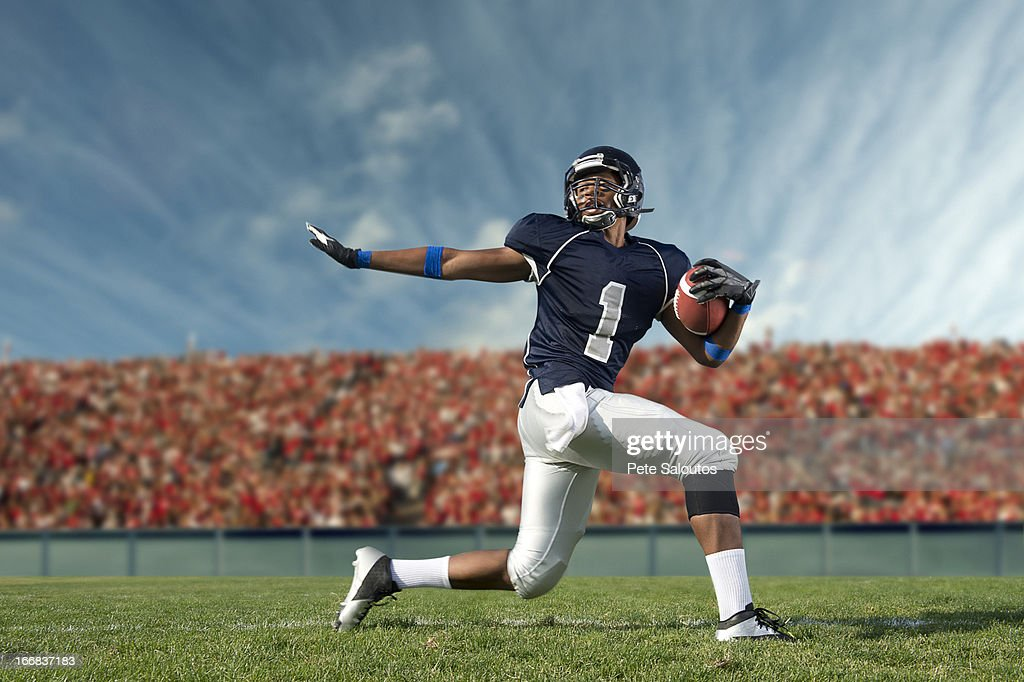 African American football player poised on field : Stock-Foto