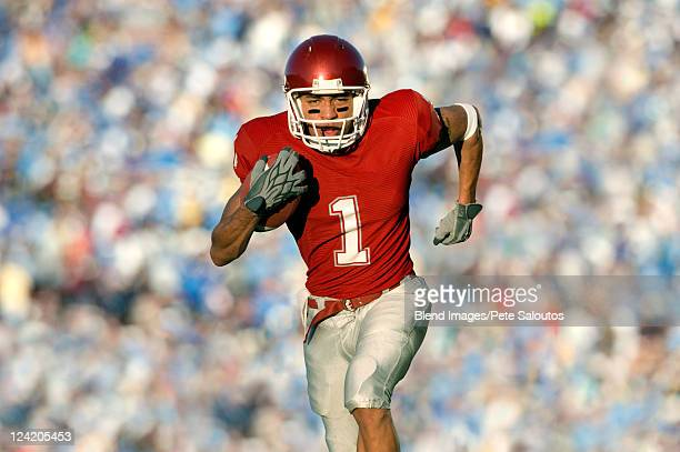 african american football player running on field in game - rush american football stock pictures, royalty-free photos & images