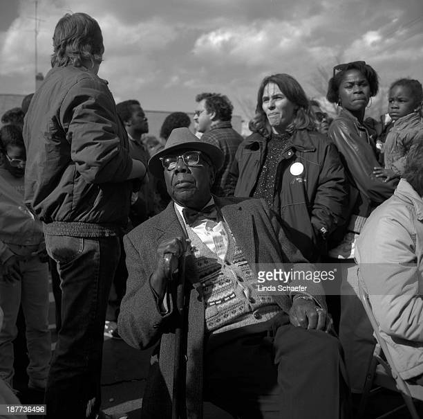 African American gentleman amidst the crowd gathered to hear the Reverend Jesse Jackson speak as a presidential candidate. Photographed in black and...