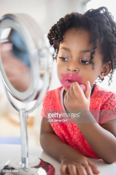African American girl applying makeup