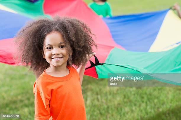 African American girl holding paracaídas en el campamento de verano