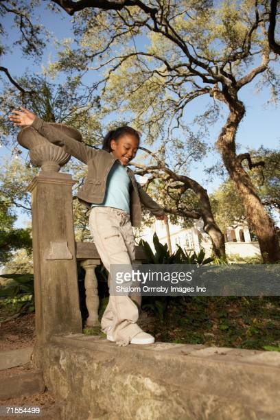 African American girl balancing on wall