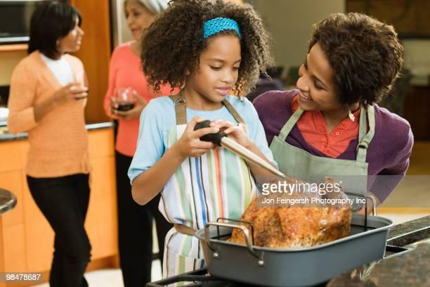 african american girl basting thanksgiving turkey - タレ ストックフォトと画像