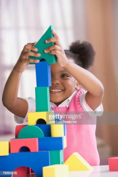 African American girl building block tower