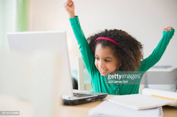 African American girl cheering at laptop