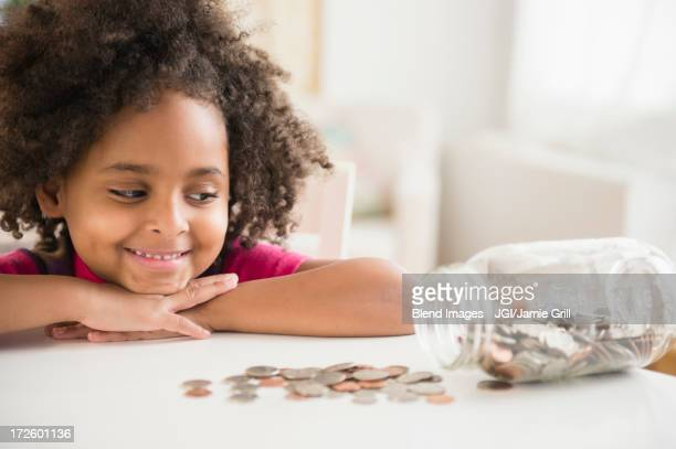 African American girl counting change in jar