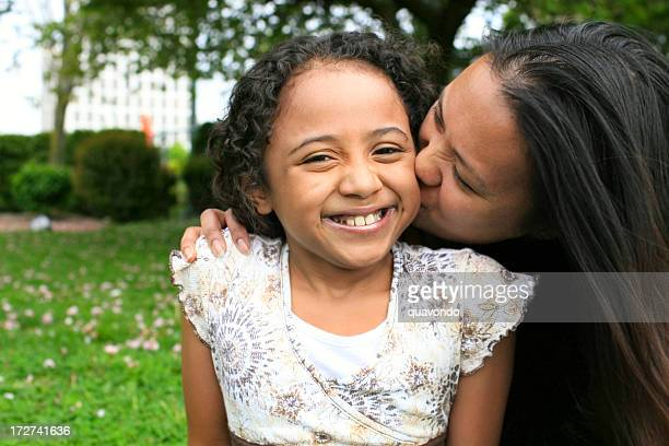 African American Girl Daughter Kissed by Mother, Outdoors, Copy Space