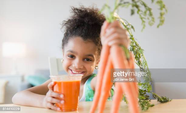 African American girl drinking carrot juice
