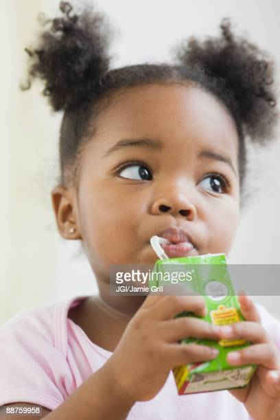 african american girl drinking juicebox - juice carton stock photos and pictures
