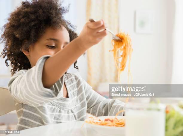 African American girl eating plate of spaghetti