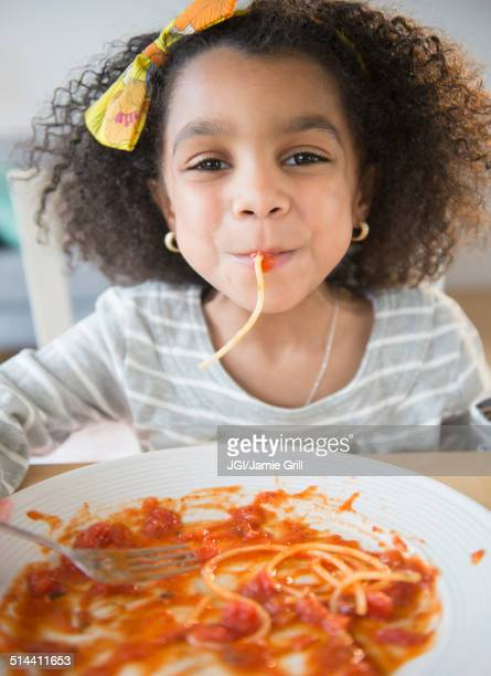 African American girl eating spaghetti at table