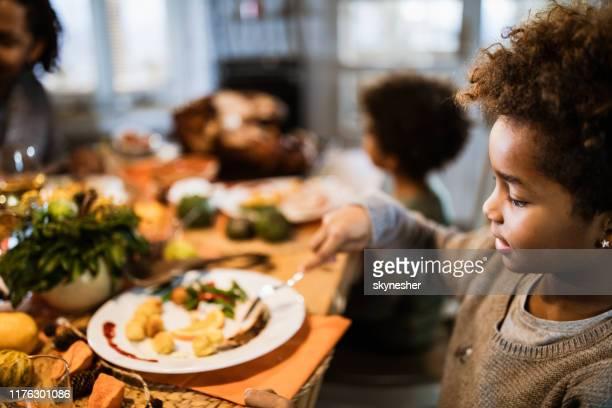 menina do americano africano que tem o almoço com sua família na sala de jantar. - african american family dinner - fotografias e filmes do acervo