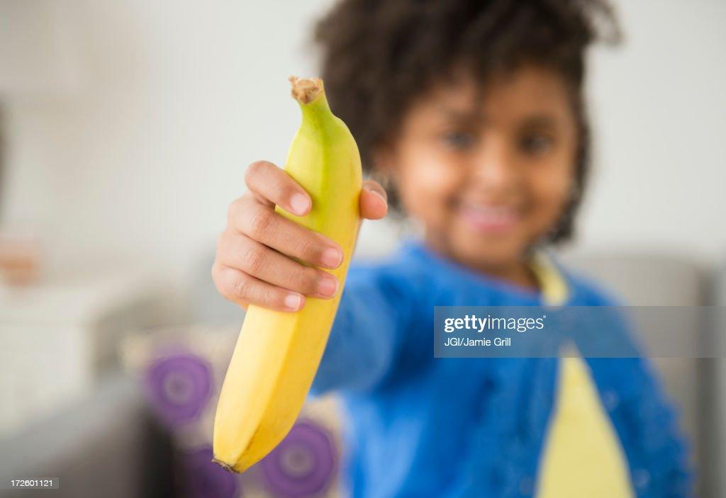 African American girl holding banana on sofa : Stock Photo