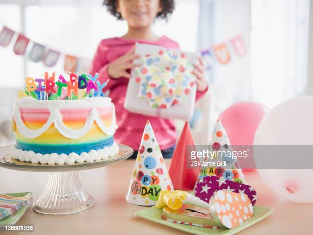 African American girl holding gift at birthday party