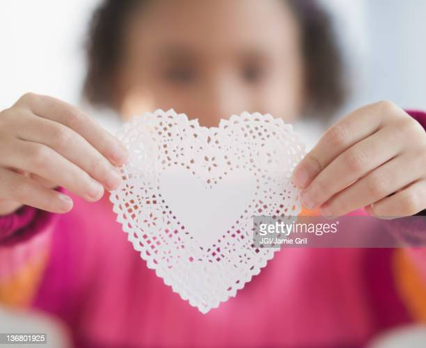 african american girl holding heart-shaped doily - doily stock photos and pictures