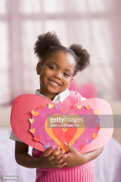 african american girl holding up cut-out paper hearts - valentines african american stock pictures, royalty-free photos & images