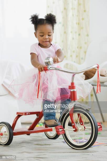African American girl in costume riding tricycle