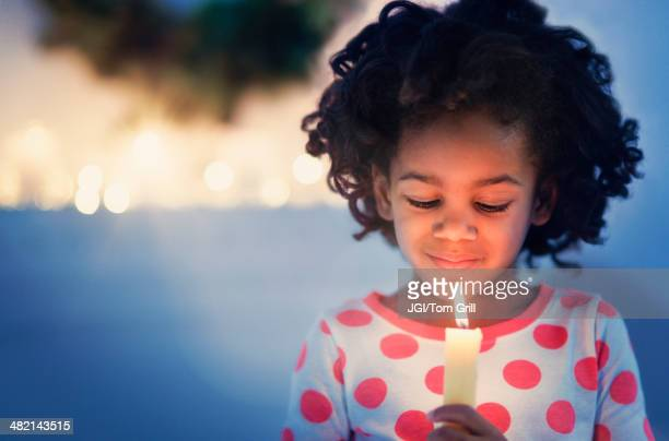 african american girl in pajamas holding lit candle - bougie espoir photos et images de collection