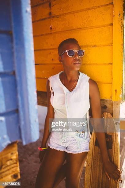 african american ragazza longboarder sulla spiaggia con sfondo colorate - afro americano foto e immagini stock