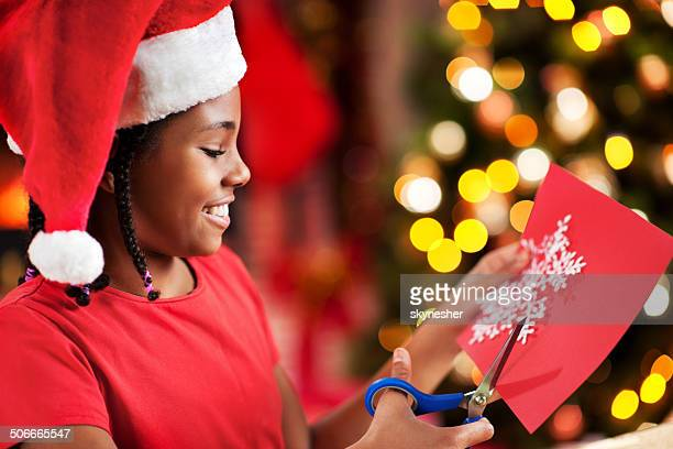 African American girl making Christmas cards.