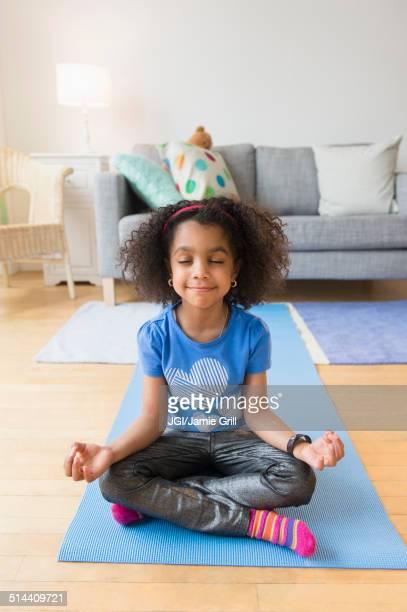 African American girl meditating on yoga mat