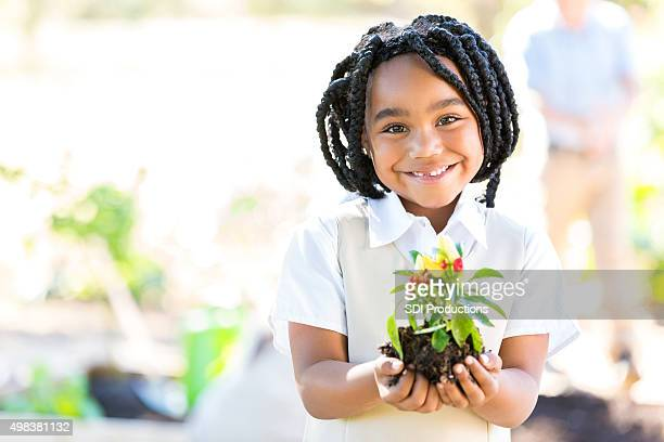 African American girl planting vegetables during field trip