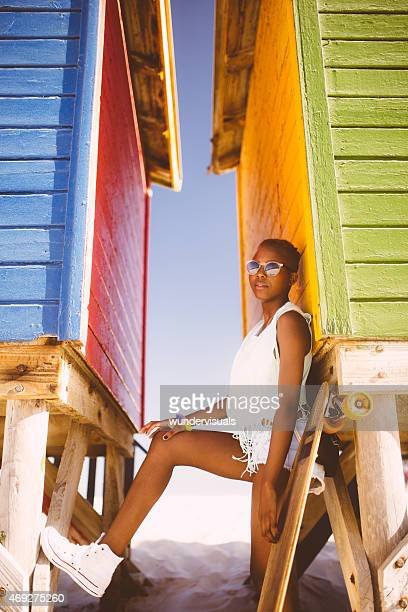 African American girl posing at the beach with her longboard