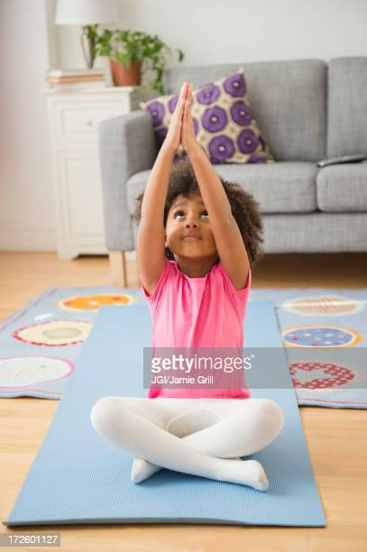 African American girl practicing yoga in living room
