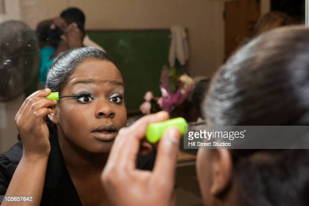 african american girl putting on mascara backstage - girl in mirror stock photos and pictures